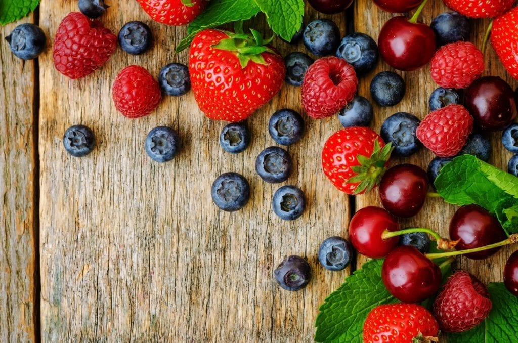 wood background with fresh berries, strawberries, blueberries, c