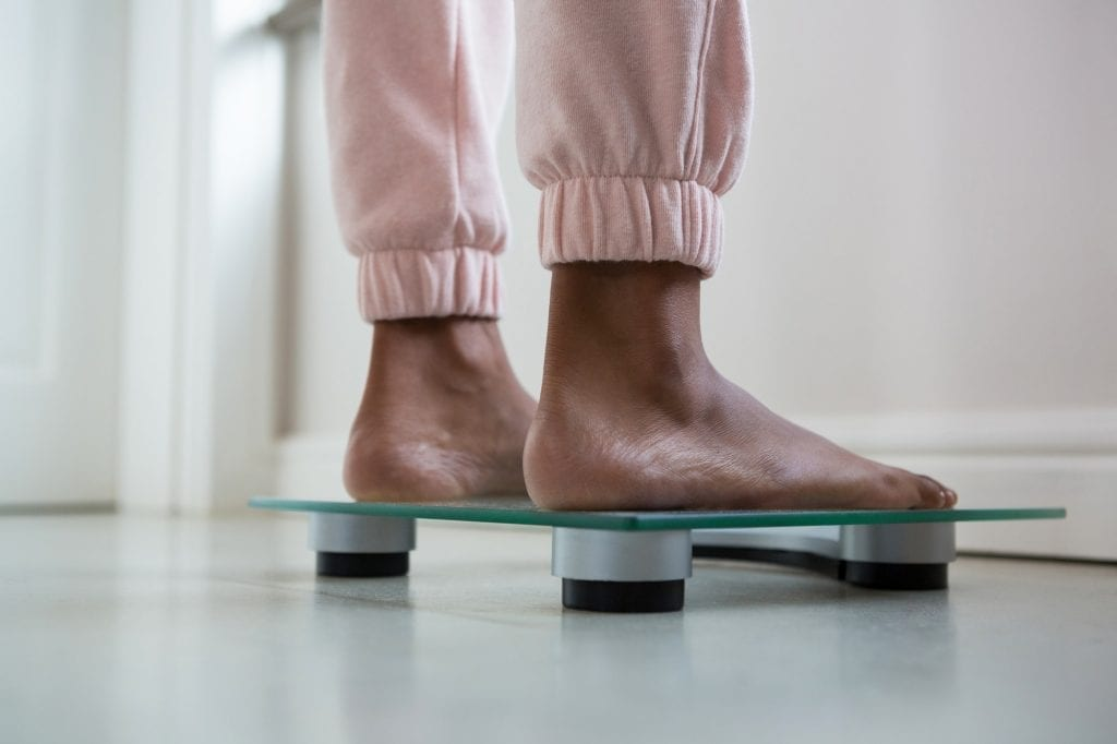 Low section of woman on bathroom scale
