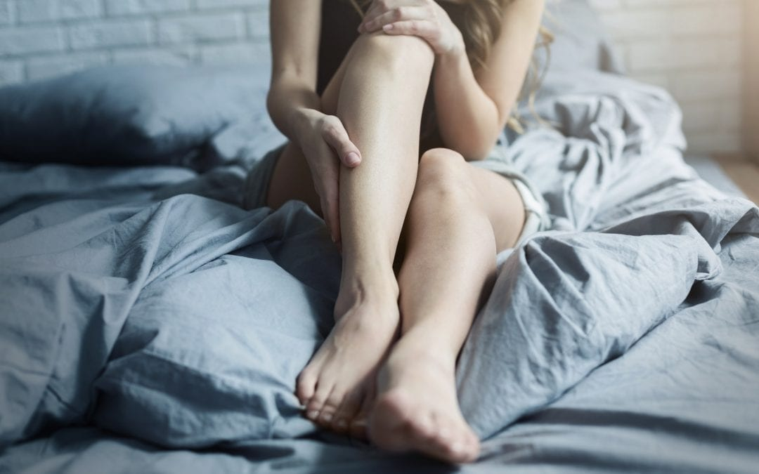 Female tired legs in bed at home