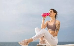 Young beautiful woman in sporty top and white leggings holding pink sport bottle drinking water with sea view on background