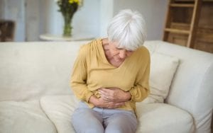 Senior woman suffering from stomach pain in living room