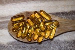 Wooden spoon holding collagen pills.